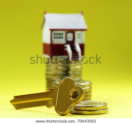 A house placed on a pile of gold coins with a golden key in front, asking the question is it time to buy that dream house?