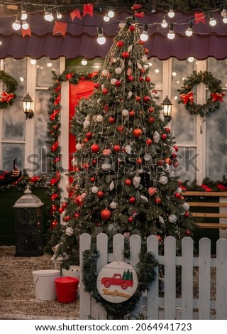 A house with a red door is decorated for Christmas. Street Christmas decor with artificial Christmas tree with Christmas veranda decorations. Soft selective focus, artistic noise.
