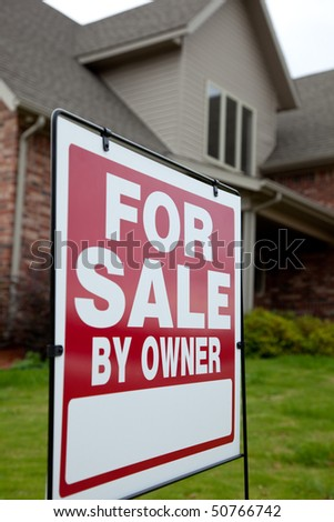 A house with a red for sale sign in the yard