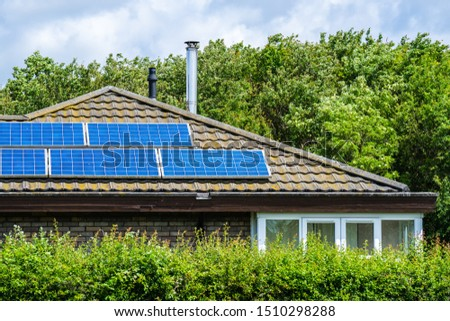 A house with a solar panels panels installed on the tile roof