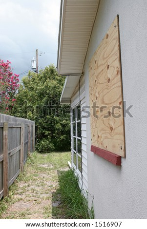 A house with plywood on the window in preparation for a hurricane.  Storm clouds overhead.  Vertical view.