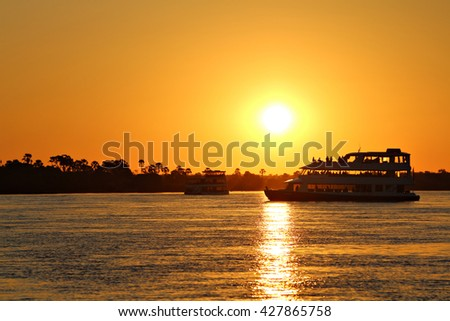 A houseboat cruises the Zambezi River, the border between Zimbabwe and Zambia, Africa, at sunset as the tourists on board enjoy sundowner cocktails. Sunset Cruise. Focus on boat. #427865758