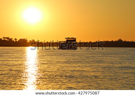 A houseboat cruises the Zambezi River, the border between Zimbabwe and Zambia, Africa, at sunset as the tourists on board enjoy sundowner cocktails. Sunset Cruise. Focus on boat.
