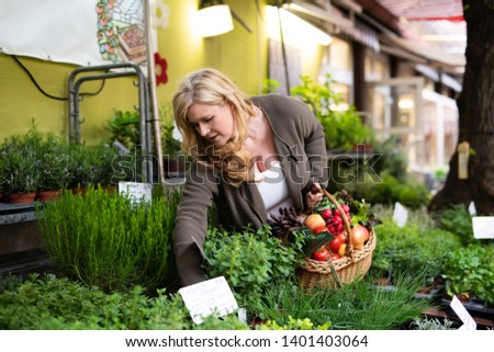 A housewife buys fresh herbs at a market #1401403064