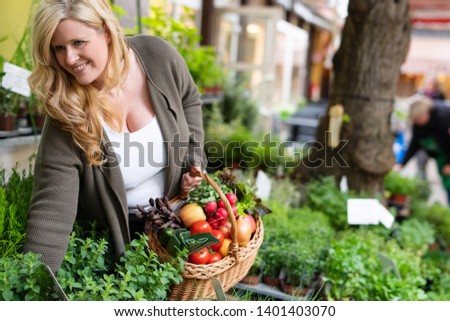 A housewife buys fresh herbs at a market #1401403070
