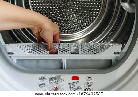 A housewife holds a lint trap from a front-loading tumble dryer. Woman's hand Stockfoto ©