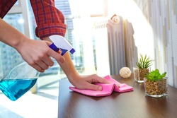 A housewife in a shirt cleans the house, wipes dust from the table with a cleaning rag and a spray. Household chores