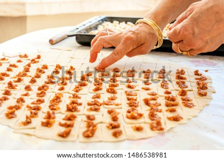 A housewife making Turkish ravioli. It is a type of dumpling popular in most Turkic cuisines as well as in the cuisines of the South Caucasus, Central Asia, Afghanistan.