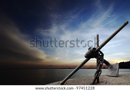 A huge Admiralty Pattern ship anchor chained onto a pier against a surreal apocalyptic evening sky. - stock photo
