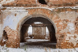 A huge arched doorway in an old abandoned brick building.