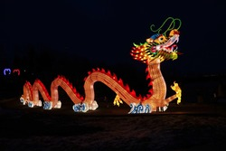 A huge bright glowing Chinese dragon Lun during the Chinese New Year celebration. Chinese Lantern Festival. Dragon is a mythical Chinese creature as a symbol of strength, wealth and power.