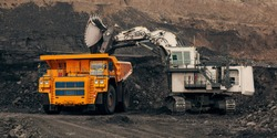 A huge excavator loads rock formation into the back of a heavy mining dump truck. Open pit coal mining.