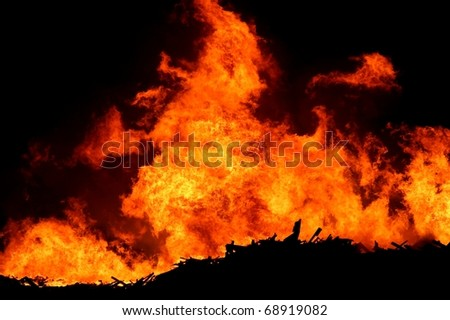 A huge fire with bright orange flames and silhouetted timber