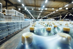 a huge industrial warehouse with plastic food wrap wrapped plastic bottles with carbonated drinks, water or beer.