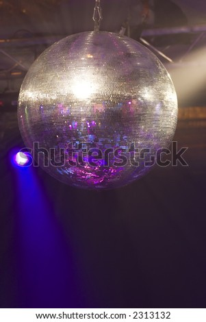 A huge mirrored glitter ball illuminated by coloured lights