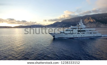 A huge motor yacht pick up small speed boat on the sunset stock photo