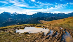 A huge muddy puddle with disgusting mud on a small path in the Carpathian mountains against the backdrop of beautiful autumn hills