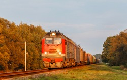 A huge new powerful diesel locomotive carries a freight train of wagons along a railway line in the rays of a summer sunset