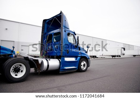 A huge number of big rig semi trucks are loaded and unloaded in the docks of huge warehouses, detaches semi trailers, attaching already loaded ones, and again the truckers kings of roads are set off #1172041684