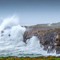 A huge ocean waves breaking on the coastal cliffs in at the cloudy stormy day. Breathtaking romantic seascape of ocean coastline.