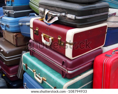 A huge pile of old suitcases in many colors piled up together.