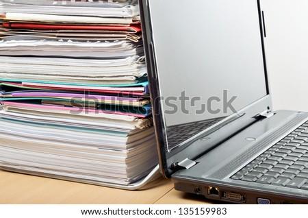 A huge pile of paperwork on a desk beside a laptop computer