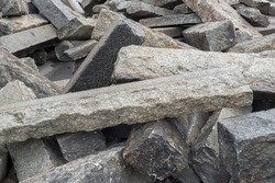 A huge pile of used concrete curbs and sleepers piled on top of each other, pulled out of the ground during road renovation work. Rectangular blocks with rough raised edges lie randomly on the ground.
