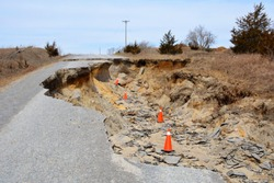 A huge section of a road is eroded by water and destroyed.