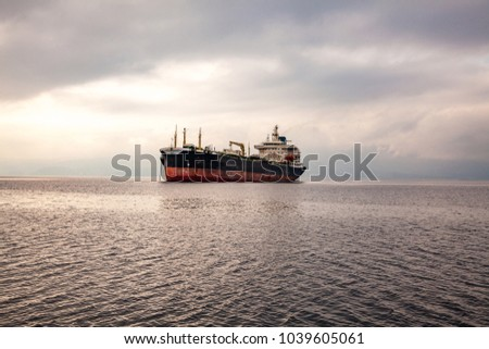 a huge ship, a dry cargo ship stands alone in a serene sea