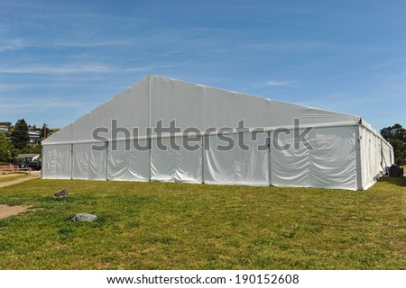 A huge tent in a grass field under sunny sky #190152608