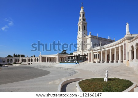 A huge tower and a marble colonnade around the square. The grand memorial and religious complex in the small Portuguese town of Fatima. - stock photo
