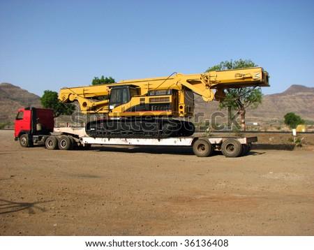 A huge truck carrying a crane.