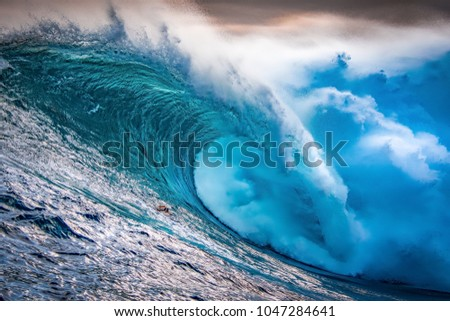A huge wave crashing at sunset during a large swell