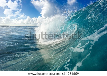A huge wave for surfing on the background of beautiful clouds. The photo was taken from the water in the Indian Ocean island of Mauritius
