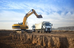 A huge yellow crawler excavator and a construction dump truck standing next to it while working on a sunny day against a blue sky. Excavator digs a pit and loads a dump truck with earth