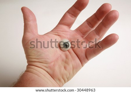 a human hand holds a genuine glass eye - stock photo