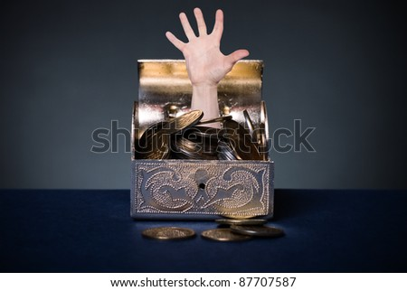 A human hand protruding from the open chest with money.