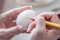 A human hands are writing with melting wax on the white surface of the egg. Preparing for the holiday Easter. The process of painting eggs with melted wax. Close up, soft focus.