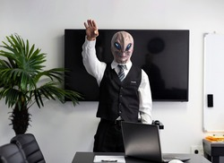 A humanoid Alien in a white shirt and business black suit in a conference, meeting room or home office raise your hand up. CEO martian putting his hand on his heart, standing, looking at camera