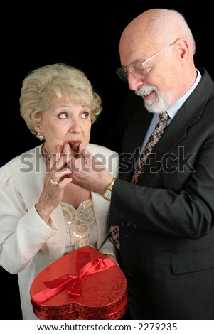 A humorous picture of a husband feeding his wife Valentine candy.  She doesn't look too sure about it.  Black background
