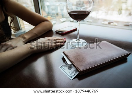 A hundred dollars generous tip on the table in a leather folder. The girl drank the wine and paid the bill. A large wine glass on the table in an expensive restaurant. the girl is waiting for waiter. Stockfoto ©