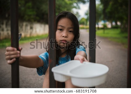 Shutterstock a hungry asian child holding an empty bowl.