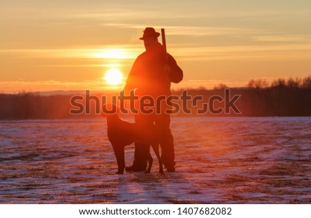 A hunter in a hat with a gun and a German shorthair pointer dog breed stands on a meadow covered with snow. Majestic winter scenery. Amazing sunrise. #1407682082