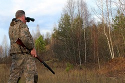 A hunter in protective clothing with a firearm observes the environment during the hunt.