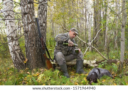 a hunter sits on a fallen tree and pours tea from a thermos, his dog lies next to him #1571964940