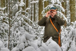 A hunter stands in the snowy forest and observes his hunting area through a small eyepiece.