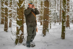 A hunter stands in the snowy spruce forest and observes his hunting area through a small eyepiece.