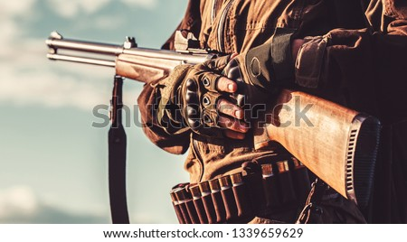 A hunter with a hunting gun and hunting form to hunt in an autumn forest. The man is on the hunt. Hunter man. Hunting period, autumn season. Male with a gun.