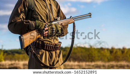 A hunter with a hunting gun and hunting form to hunt. The man is on the hunt. Hunting period. Male with a gun. Hunter with a backpack and a hunting gun. Hunter man.