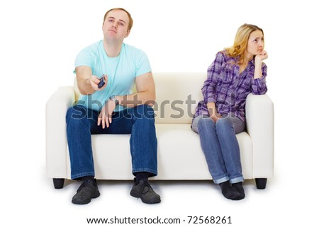 A husband and wife in a quarrel sit on the couch watching TV isolated on white background